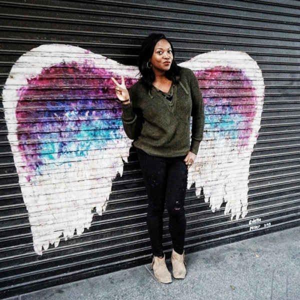 Stylist Melissa Chataigne posing with Angel wings street mural at in dtla fashion district in lace up sweater